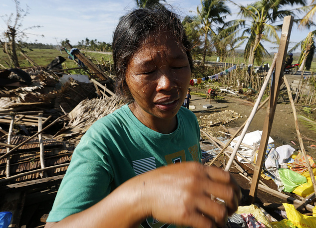 Photo: Pilipino typhoon victim cries as she views what is left of her home in the typhoon hit town, Samar island, Philippines, 08 December 2014