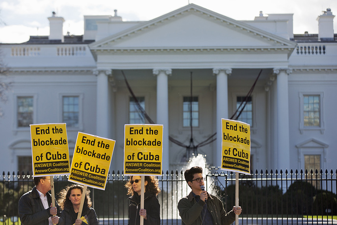 "Photo: People from the ANSWER Coalition (Act Now to Stop War and End Racism) hold signs urging the US to ""End the blockade of Cuba,"" during a demonstration outside of the White House in Washington, December 17, 2014"