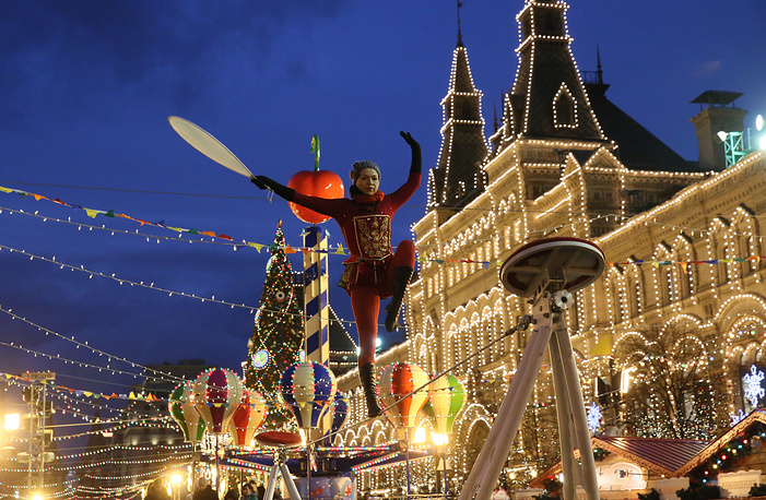 A ropewalker performs in Moscow's Red Square with the illuminated GUM department store in the background