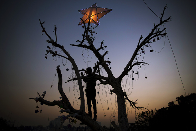 Pakistani Christian boy decorates a tree in preparation for the upcoming Christmas holiday in Islamabad's slums, Pakistan