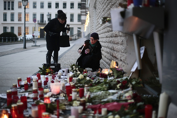 Women light candles in front of the French Embassy in Berlin, Germany