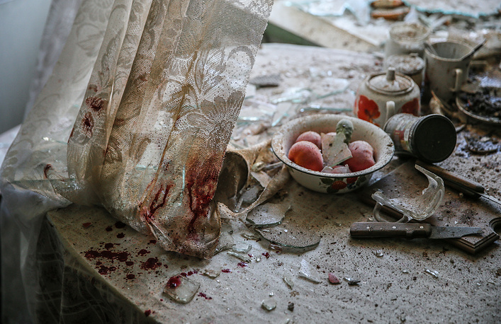 Picture by photographer Sergei Ilnitsky of European Pressphoto Agency (EPA), showing blood stains on a table and curtain and damaged dishes and goods in a home in downtown Donetsk, Ukraine, won 1st Prize in General News Singles category of the 58th World Press Photo Contest