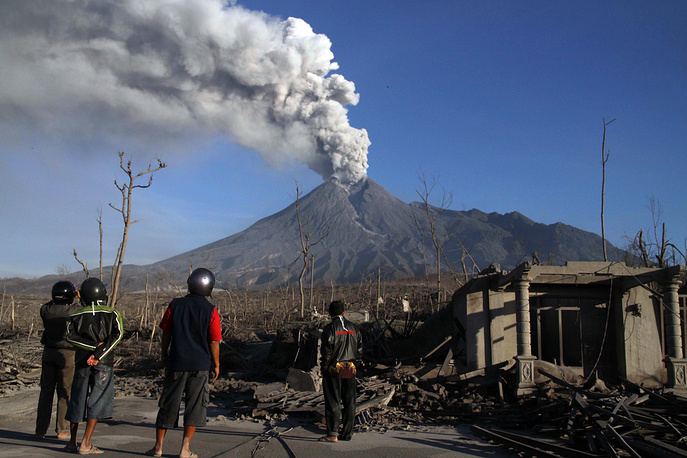Eraption of Mount Merapi in Indonesia began in late October 2010. Photo: Indonesian men looking at Mount Merapi erupting in the Bimomartani Village, Sleman, Indonesia on 14 November 2010