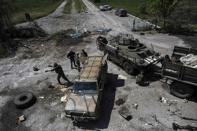 Ukrainian soldiers repairing armed vehicles near the division line in Maryinka, near Donetsk