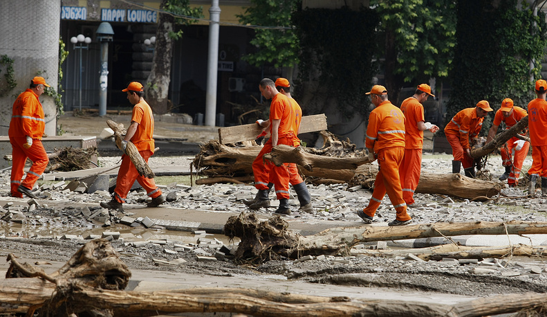 Municipal workers cleaning an area around a flooded zoo area