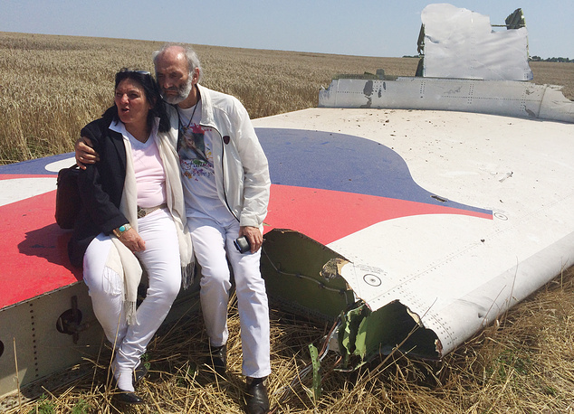 Parents of a young girl, who was a passenger on Malaysia Airlines flight MH17, sitting on part of the wreckage of the crashed aircraft in Hrabove, Ukraine