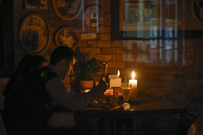 A man eating by candlelight in a cafe after a power failure, in Simferopol