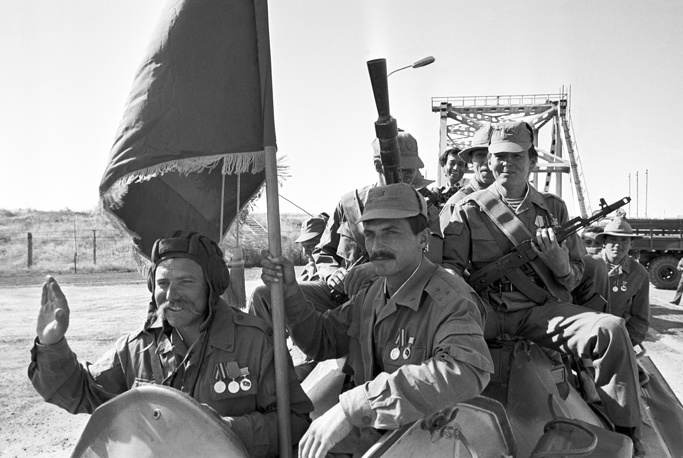 The first Soviet soldiers-internationalists react as they crossed the Friendship Bridge (back) over Amu Darya river on the Afghan-Soviet (Afghan-Uzbek) border, 1988