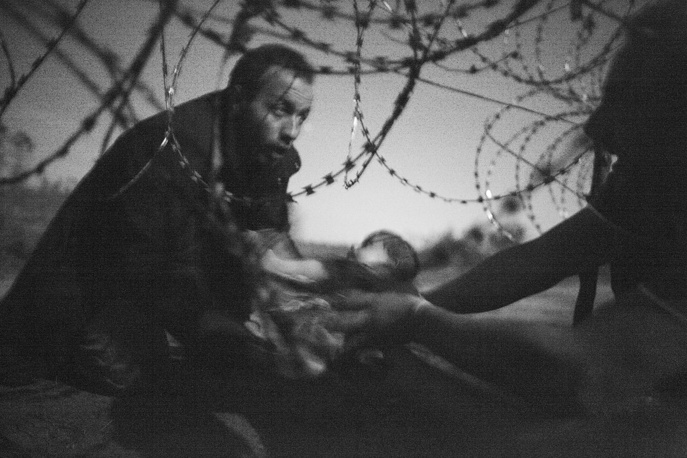 Australian photographer Warren Richardson won the World Press Photo of the Year award and 1st prize singles in the Spot News category. The picture shows man passing a baby through the fence at the Serbia/Hungary border in Roeszke, Hungary, 28 August 2015