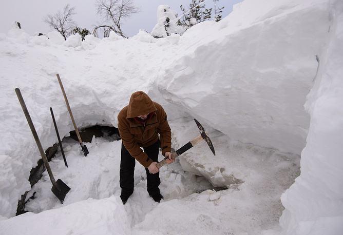 A Buddhist community member chops ice to get fresh water on Mount Kachkanar