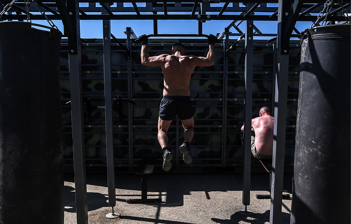 Russian soldiers doing physical exercises at an outdoor gym