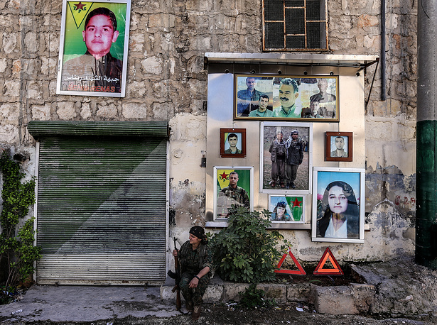Kurdish soldier sitting beneath portraits at a memorial to fellow soldiers who have been killed in the Syrian Civil War, in the Sheikh Maksoud neighbourhood of Aleppo