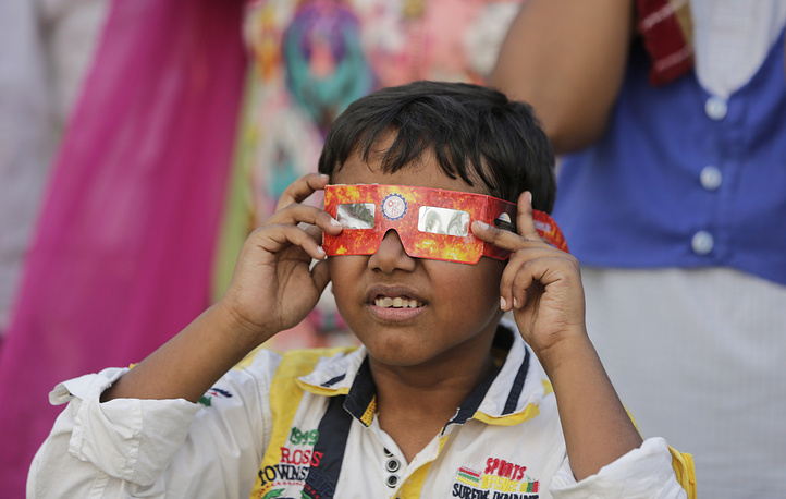 A boy uses a a goggle made of cardboard to watch the transit of Mercury across the sun in Lucknow, India