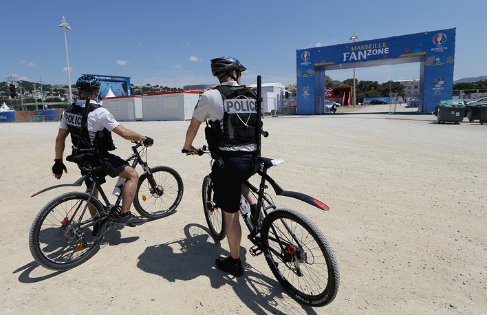 Policemen ride their bikes as they patrol near the fan zone at the Prado beach, in Marseille, southern France
