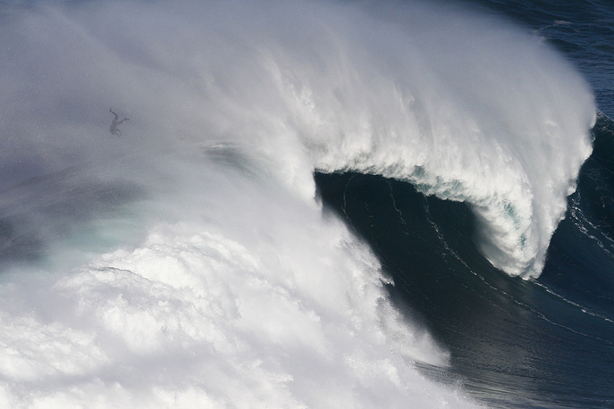 A surfer is caught by a big wave at Praia do Norte at Nazare, Portugal, October 24