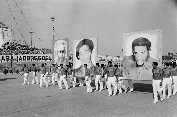 """Years later, on April 16, 1961 Fidel Castro officially declared the socialist nature of Cuban Revolution. Photo: Cuban athletes carrying portraits of Karl Marx, Raul Castro, and Ernest """"Che"""" Guevara, during May Day parade in Havana, May 1, 1961"""