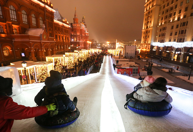 People slide down an icy slope between Manege and Revolution Squares in Moscow