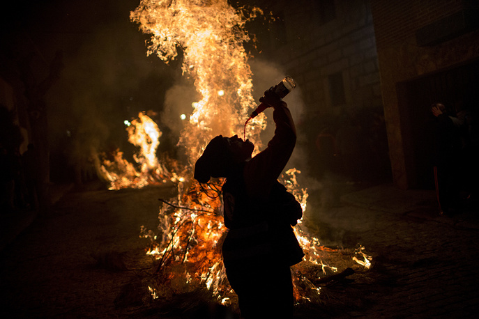 A woman drinks wine next to a bonfire as part of a ritual in honor of Saint Anthony the Abbot, the patron saint of domestic animals, in San Bartolome de Pinares, Spain, January 16