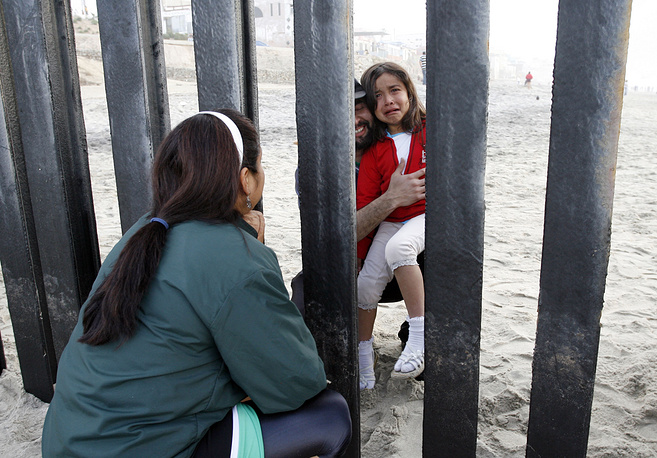 Mexican family, separated by the wall, meets near the US-Mexico border fence at Border Field State Park in San Diego, USA, 2009