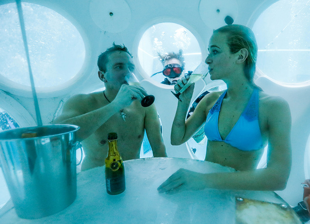 """People drink champagne while sitting inside """"The Pearl"""", a spheric dining room placed 5 metres underwater in the NEMO33 diving center, one of the world's deepest pools (33 metre) built to train professional divers, in Brussels, Belgium, January 31"""