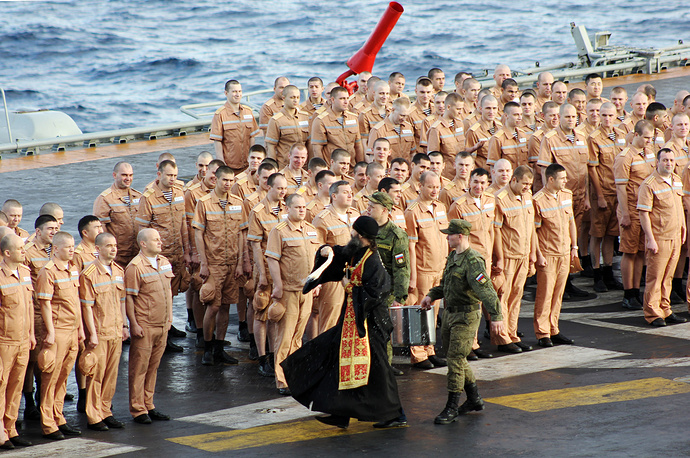 A Russian Orthodox priest and Russian servicemen on the Admiral Kuznetsov aircraft carrier, October 20, 2016