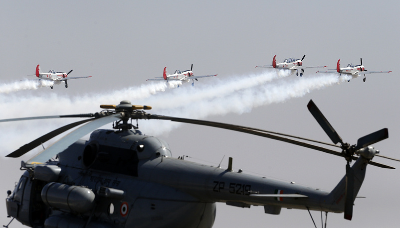 The Yakovlevs, a UK based aerobatic team flying Russian designed Yakovlev aircrafts, fly over an Indian Air Force helicopter