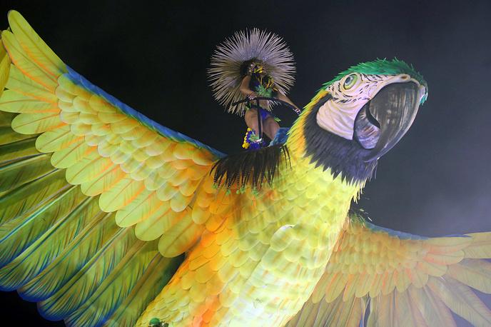 A member of the samba school dances on a parrot figure on top of a float during a parade held during Rio de Janeiro's Carnival