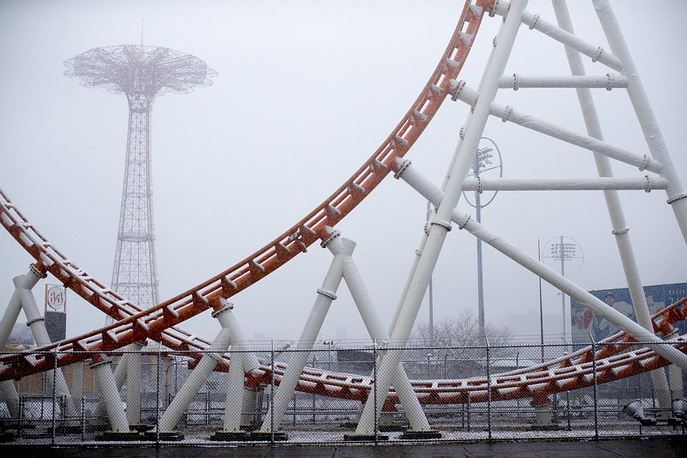 The Parachute jump ride is framed by the Thunderbolt roller coaster as snow falls in New York's Coney Island