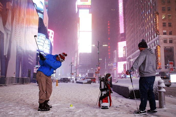Two men play golf with a tennis ball as a snowstorm sweeps through Times Square, New York, March 14