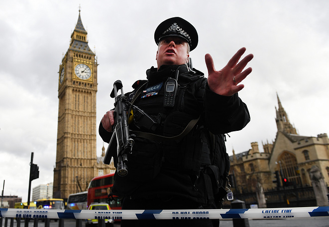 Armed police push people back following the incidents outside the Houses of Parliament in London, Britain