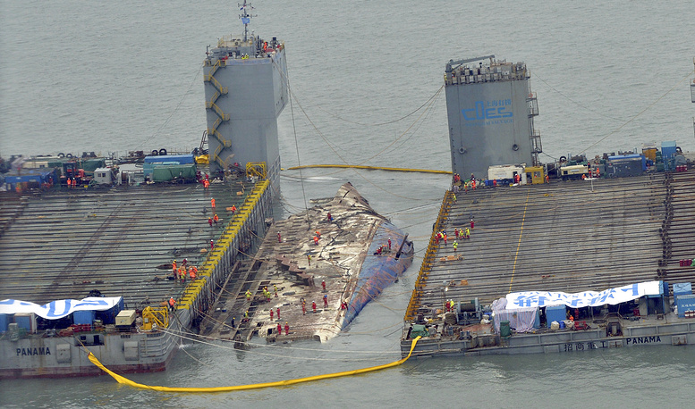 Workers prepare to lift the sunken Sewol ferry (center) in the waters off Jindo, South Korea, March 23