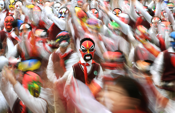 Students wearing traditional opera masks attend an exercise session in Wuhan, Hubei province, China, March 28