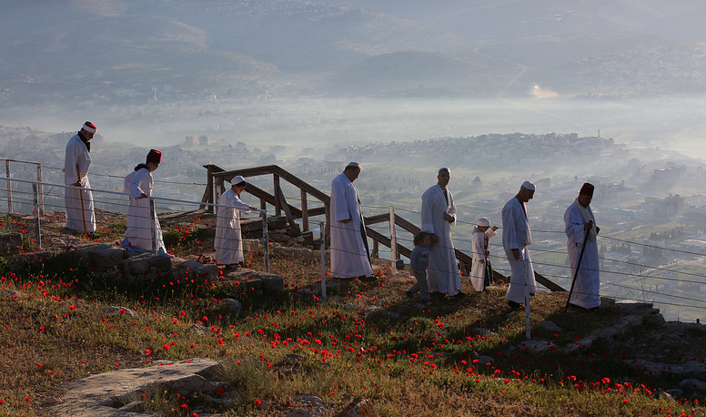 Members of the Samaritan community gather to pray at sunrise during a religious service marking the end of their Passover holiday atop Mount Gerizim, above the city of Nablus, in the West Bank, April 17