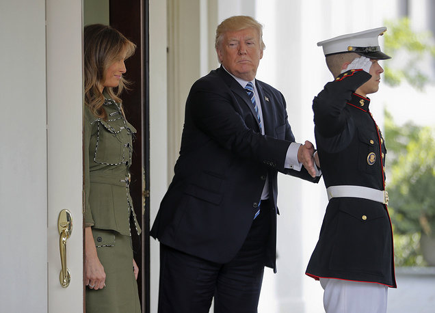 US President Donald Trump pats a US Marine on the back after he and first lady Melania Trump walked Argentine President Mauricio Macri and his wife Juliana Awada to their vehicle outside the West Wing of the White House in Washington, April 27