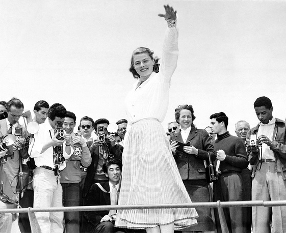 Ingrid Bergman is snapped from all sides by a crowd of photographers at Cannes, 1956
