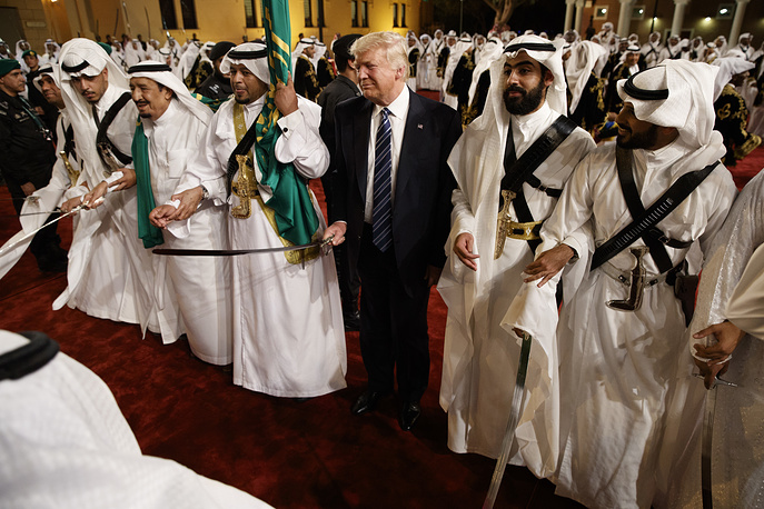 Donald Trump holds a sword and sways with traditional dancers during a welcome ceremony at Murabba Palace, Riyadh
