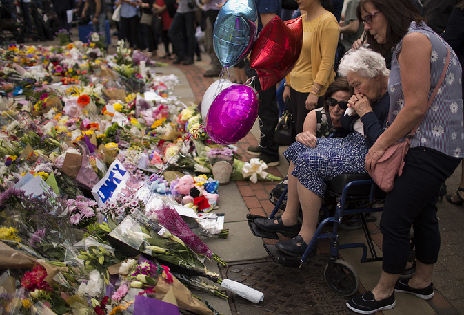 Women cry after placing flowers in a square in central Manchester after the suicide attack at an Ariana Grande concert, Britain, May 24