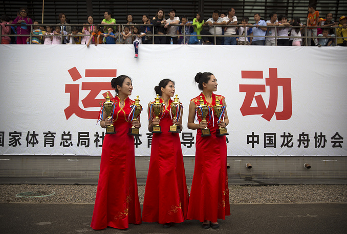 Hostesses stand with trophies as they wait for an awards ceremony at the Olympic Water Park in Beijing