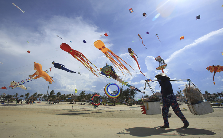 A food vender walks under flying kites on Tam Thanh beach during an International Kite Festival in Quang Nam province, Vietnam, June 11