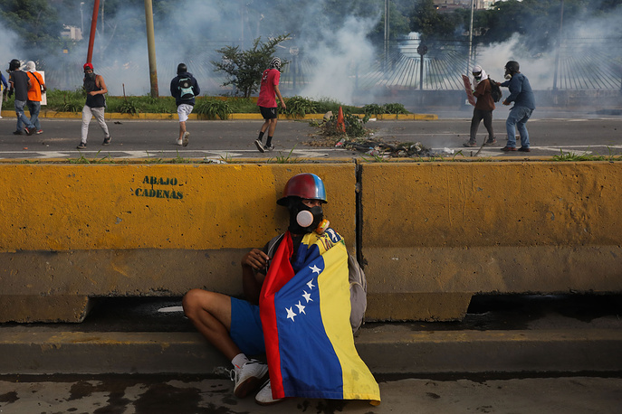 A protester hides behind a wall during protests in Caracas, Venezuela, June 22