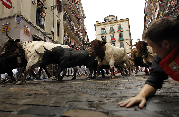 Revellers run in front of Fuente Ymbro's fighting bulls during the running of the bulls at the San Fermin Festival