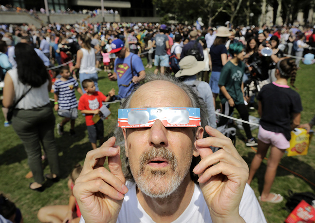A man uses protective eclipse glasses to view a partial solar eclipse on the campus of Massachusetts Institute of Technology, in Cambridge