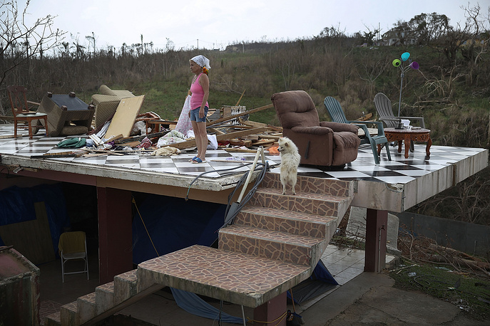 A woman stands with her parrot and her dog in what is left of her home that was destroyed when Hurricane Maria passed through in Corozal, Puerto Rico, September 27