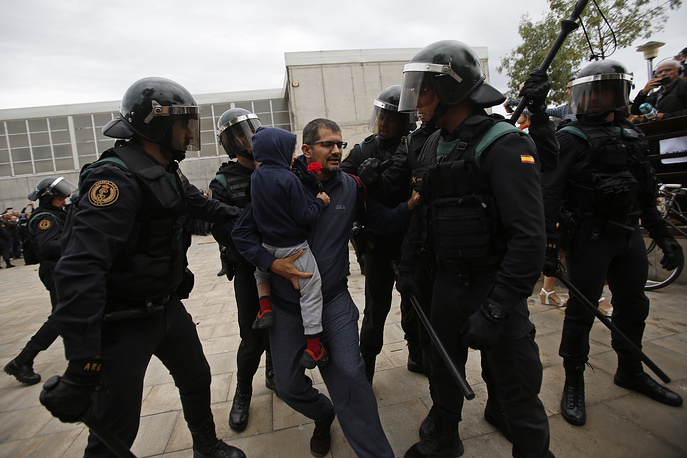 Civil guards force a man with a child to leave the entrance of a sports center, assigned to be a referendum polling station by the Catalan government in Sant Julia de Ramis, near Girona
