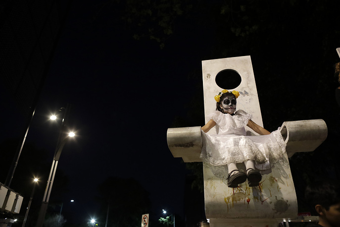 "A girl dressed as Mexico's iconic ""Catrina"" sits on a piece of public art during a march in the Grand Procession of the Catrinas in Mexico City"