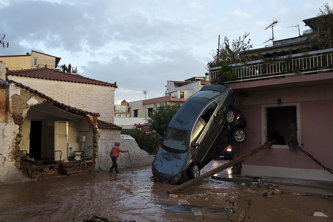 A woman walks on a flooded street next to damaged houses and flipped over cars in the municipality of Madra western Athens, November 15