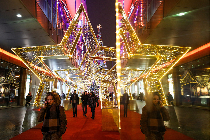 People walk though a star-shaped light tunnel in Moscow