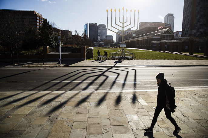 A woman passes by a menorah on Independence Mall in Philadelphia ahead of the second night of Hanukkah, USA, December 13