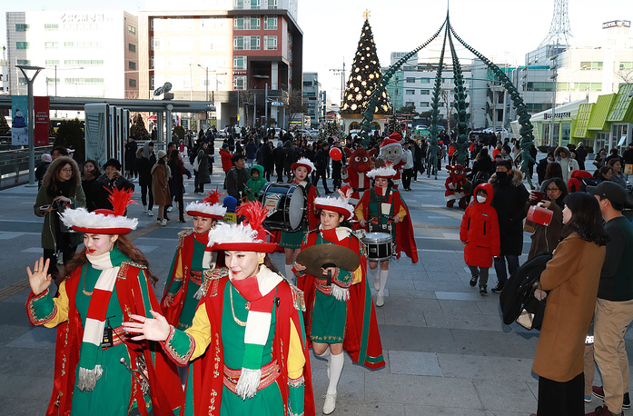 Holiday shoppers watch a Christmas Day parade at a major shopping mall in Seoul, South Korea