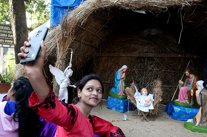 A girl takes a selfie with a nativity scene behind her during a morning mass at a church in Bhopal, India. Although Christians represent only a bit more than two percent of the Indian population, Christmas Day is celebrated throughout the country